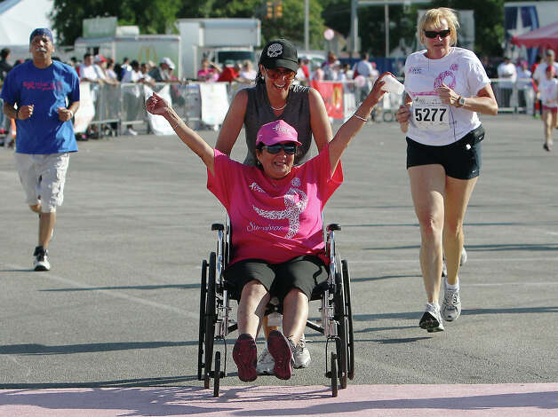 Mary Jane Reyna, seated in a wheelchair, celebrates crossing the finish line while being assisted by her sister, Patricia Martinez, at the 2012 Susan G. Komen San Antonio Race for the Cure on Saturday, May 12, 2012. Reyna said she has been cancer-free for three years. Kin Man Hui/Express-News. Photo: Kin Man Hui, Express-News / San Antonio Express-News
