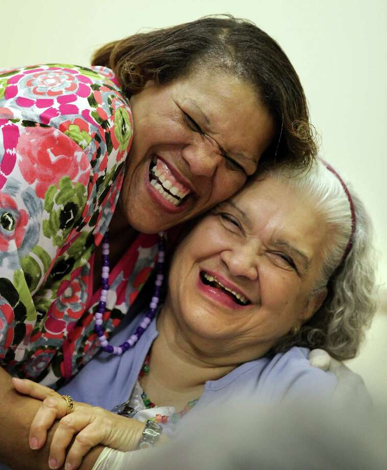 "Liz Laird, left, Assistant Activity Director at Grace Place Alzheirmer's Center, greets Janie C. with a Happy Mother's Day hug at a ""Tea Party"" and Dance for mothers enrolled at the center.  Grammy nominee Mark Little, and Jan Halsema provided live music for the seniors' enjoyment and dance.  Friday, May 11, 2012. Photo/Bob Owen Photo: BOB OWEN, Express-News / © 2012 San Antonio Express-News"