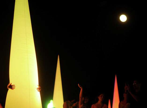 A person hugs a lighted cone display as the super full moon shines overhead during Luminaria 2012 in Hemisfair Park on Saturday, May 5, 2012. Billy Calzada / San Antonio Express-News Photo: BILLY CALZADA, Express-News / SAN ANTONIO EXPRESS-NEWS
