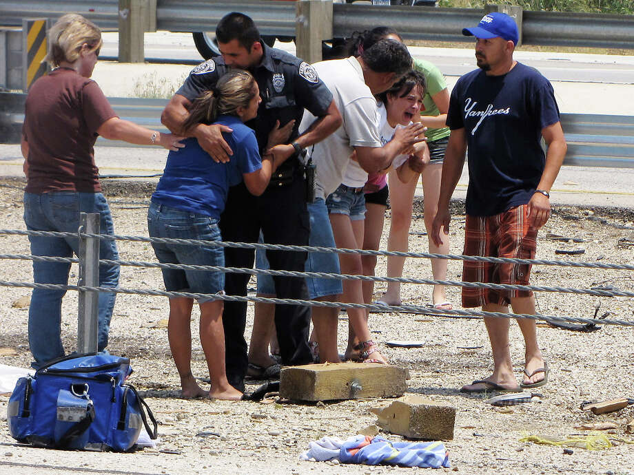 Relatives react at the scene of a rollover crash that killed two children on the South Side Sunday afternoon. A boy and a girl were ejected from an SUV as it rolled over after a tire blew out on Interstate 35; the driver of the SUV fled the scene. Sunday, May 6, 2012. Photo: Express-News / emoravec@express-news.net