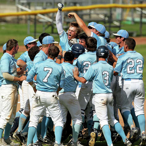 Cody Dunlap surges out of a pile of teammates surrounding him after he hit a deep fly in the seventh inning to drive in the winning run as Johnson beats South San 5-4 in the final game of a three game series at South San High School on May 12, 2012.  Tom Reel/ San Antonio Express-News Photo: TOM REEL, Express-News / San Antonio Express-News