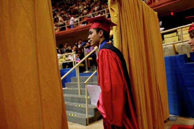 Travis Early College High School valedictorian Andrew De Luna walks into the arena at the start of the graduation procession to take his seat on the stage for his speech as he and his fellow Travis Early College High School students graduate with San Antonio College at Freeman Coliseum on Saturday, May 12, 2012. Photo: Lisa Krantz, SAN ANTONIO EXPRESS-NEWS / SAN ANTONIO EXPRESS-NEWS
