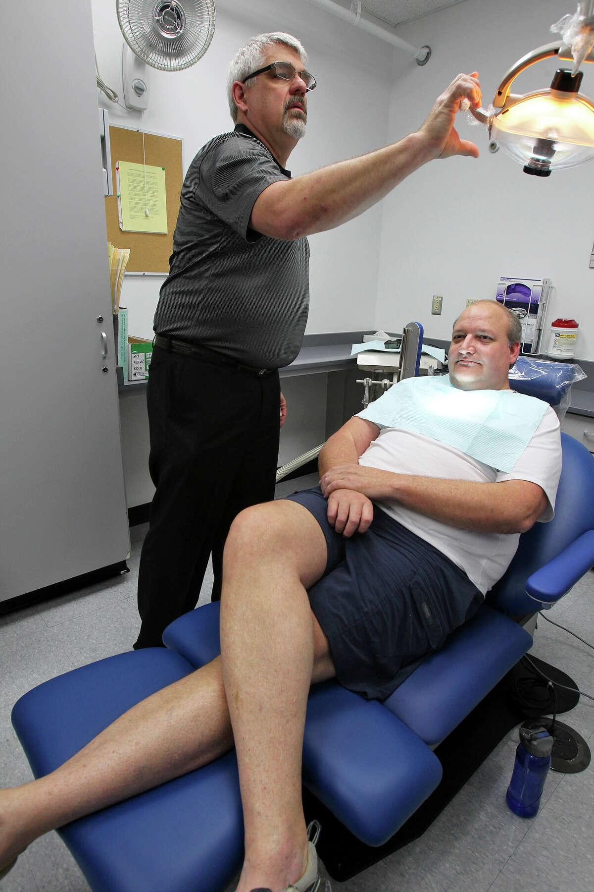 """Diaco Dental representative Brian Trewella demonstrates as George Booth, a 6'5"""", 300 lbs. plus guy, rests in a new large size dental chair at the University of Texas Helath Science Center Dental School on May 9, 2012."""