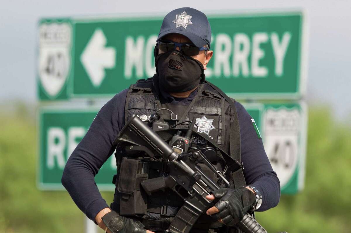 A Mexican federal police officer guards the area where 49 headless, handless bodies were found near a highway connecting Monterrey to the U.S. border.