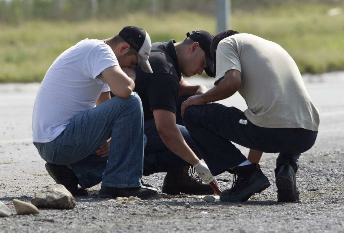 Forensic experts examine the area where 49 mutilated bodies were found near a highway connecting Monterrey to the U.S. border. Officials blamed the deaths on the Zetas gang.