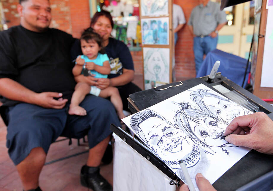Mel Lothrop draws a caricature of Miguel Delgado, (from left), daughter Nevaeh Delgado, 15 months, and mother Jewels Rodriguez in Market Square Sunday May 13, 2012 during the Mother's Day Week-end Celebration. Photo: EDWARD A. ORNELAS, SAN ANTONIO EXPRESS-NEWS / © SAN ANTONIO EXPRESS-NEWS (NFS)