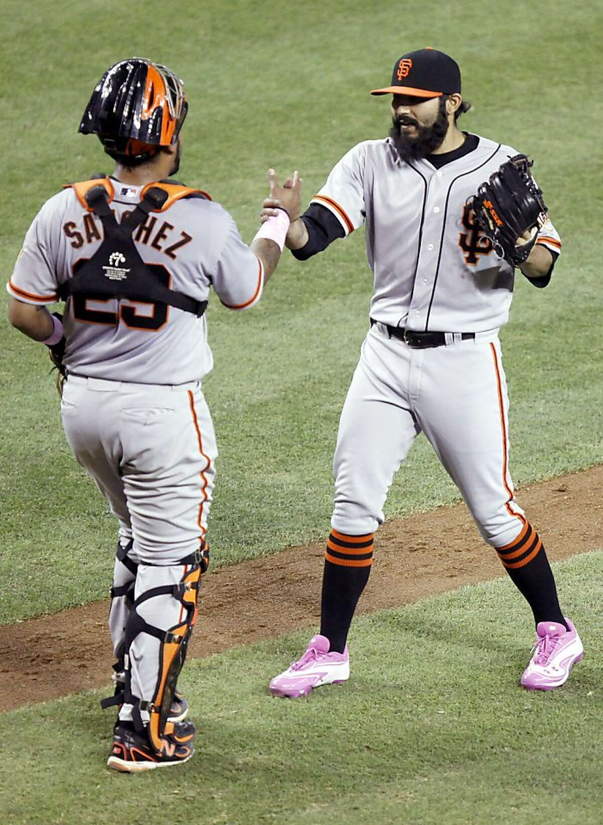 San Francisco Giants pitcher Sergio Romo, right, is congratulated by catcher Hector Sanchez, left, after defeating the Arizona Diamondbacks in the ninth inning of a baseball game Sunday, May 13, 2012, in Phoenix. The Giants won 7-3.(AP Photo/Paul Connors)