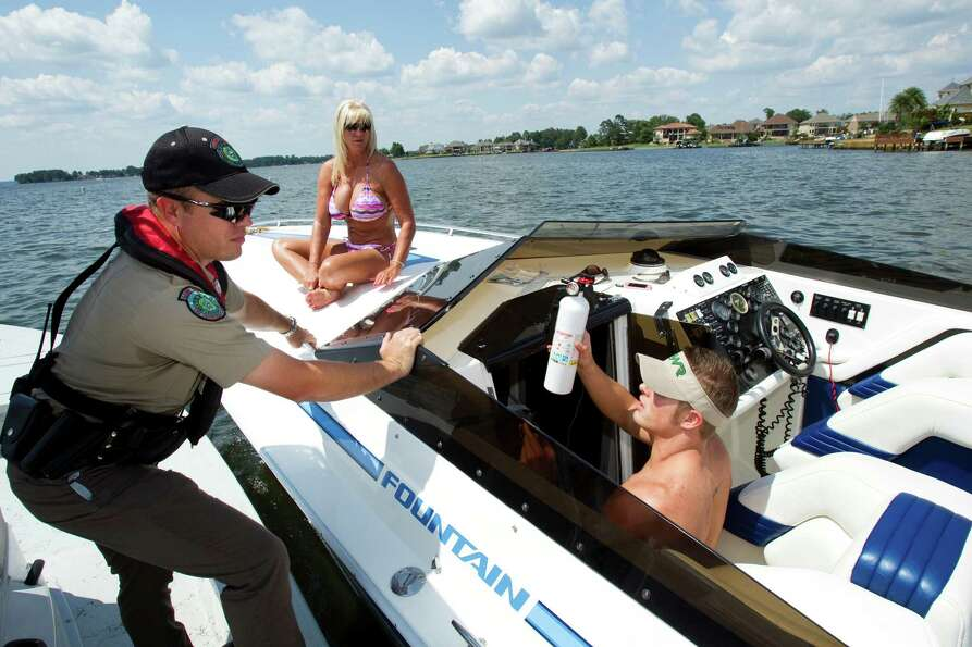 Game Warden Brannon Meinkowsky, left, talks to boater Derek Barber as he does a safety check on Lake