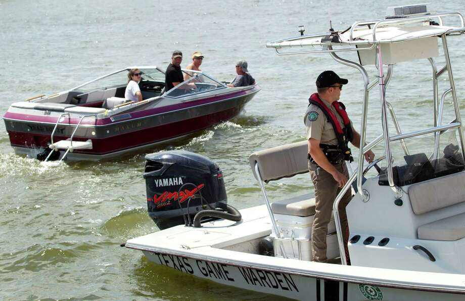 Game Warden Brannon Meinkowsky, left, patrols on Lake Conroe Sunday, May 13, 2012, in Conroe. Photo: Brett Coomer, Houston Chronicle / © 2012 Houston Chronicle