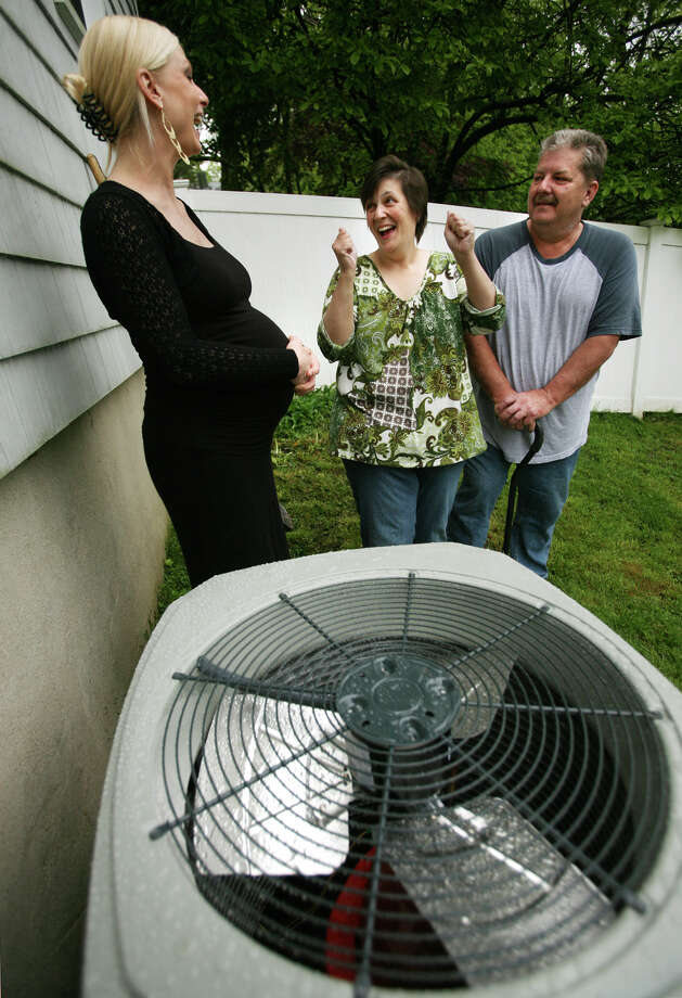 "From left; Megan Smith-Gill, director of sales and marketing for Gault Energy, talks with contest winners Kathy and Ed Lane of Norwalk by their new Trane high efficiency central air conditioning system on Wednesday, May 9, 2012. Lane decribes her reaction when she found out she had won the ""Home Sweat Home"" essay contest. Photo: Brian A. Pounds / Connecticut Post"