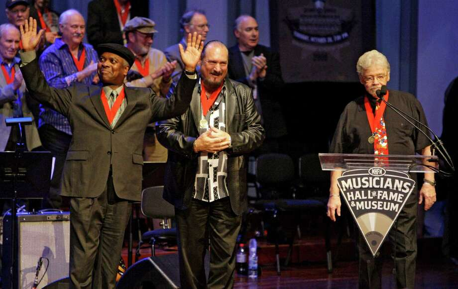 "FILE - In this Oct. 28, 2008 file photo, Booker T. Jones, left, Steve Cropper, center, and Donald ""Duck"" Dunn, right, of the group Booker T. & the MGs, acknowledge the applause as they are inducted into the Musicians Hall of Fame in Nashville, Tenn. Bass player and songwriter Dunn died in Tokyo, Sunday May 13, 2012. He was 70. (AP Photo/Mark Humphrey, File) Photo: Mark Humphrey / AP2008"