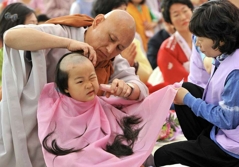 "A South Korean boy gets his head shaved by a Buddhist monk during a ""Children Becoming Buddhist monks"" ceremony at Jogye temple in Seoul on May 13, 2012. The 9 children will stay at the temple to learn about Buddhism for 20 days ahead of celebrations for Buddha's birthday on May 28 this year. Photo: JUNG YEON-JE, AFP/Getty Images / AFP"