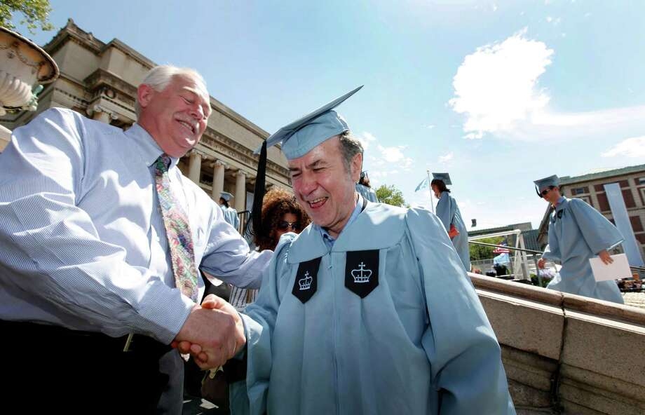 Columbia University janitor Gac Filipaj is congratulated by his boss, Donald Schlosser, the assistant vice president of facility operations, during his graduation Sunday from the Columbia University School of General Studies. Photo: Jason DeCrow / FR103966 AP