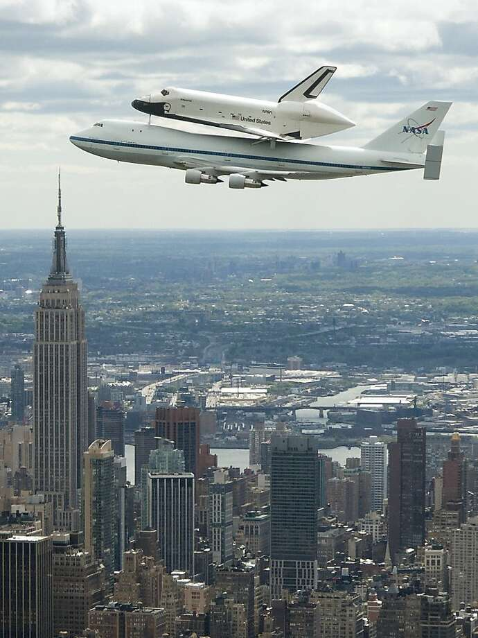 FILE - In this April 27, 2012, file photo, provided by NASA, space shuttle Enterprise, riding on the back of the NASA 747 Shuttle Carrier Aircraft, flies over New York near the Empire State Building, left.  Enterprise has been separated from the NASA 747 Shuttle Carrier at John F. Kennedy International Airport, just weeks after flying over New York City. Next month it will be taken by barge to the aircraft carrier USS Intrepid, the floating air-and-space museum that will be the shuttle's permanent home. The shuttle is scheduled to open to the public in mid-July. (AP Photo/NASA, Robert Markowitz, File) Photo: Robert Markowitz, Associated Press