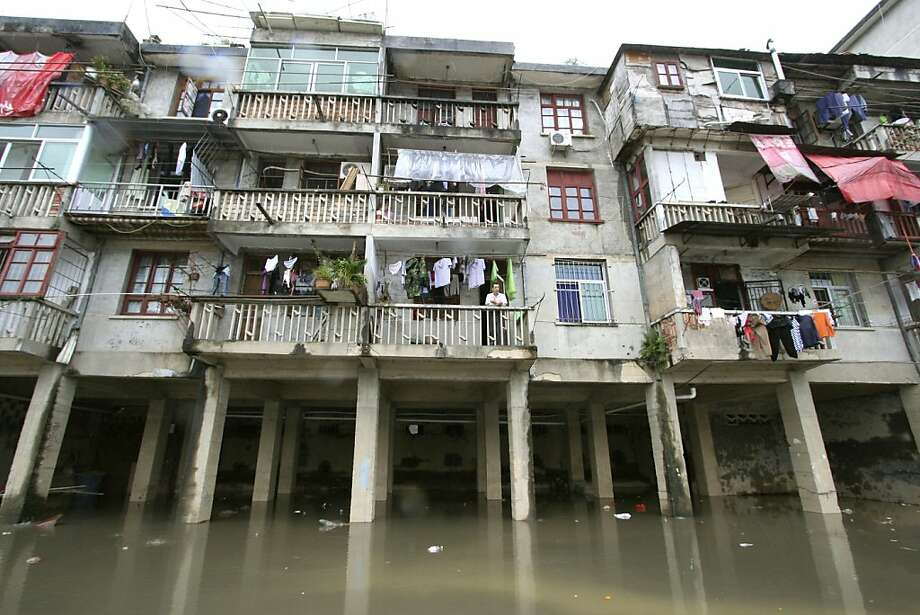 In this photo released by China's Xinhua News Agency, a resident stands on the balcony of his family's apartment as the building is partly submerged by floodwaters in Shunchang County, southeast China's Fujian Province, on Sunday, May 13, 2012.  (AP Photo/Xinhua,Chen Baicai) NO SALES Photo: Chen Baicai, Associated Press