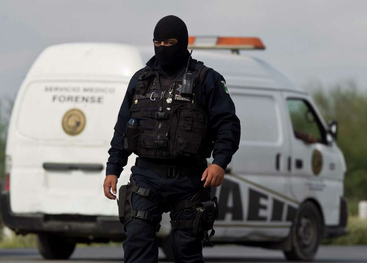 A federal policeman guards the scene where dozens of mutilated bodies were found on a highway connecting the northern Mexican metropolis of Monterrey to the U.S. border.