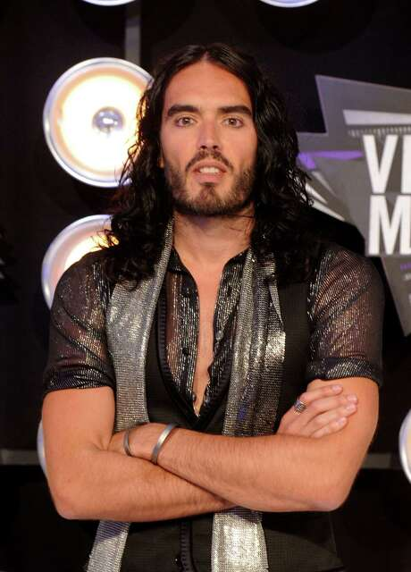 LOS ANGELES, CA - FILE:  Comedian Russell Brand arrives at the 2011 MTV Video Music Awards at Nokia Theatre L.A. LIVE on August 28, 2011 in Los Angeles, California. Brand turned himself into New Orleans police on Thursday after an arrest warrent was filed for Brand for throwing a photographer's iPhone through a window. He has been charged with simple criminal damage and is being held on $5,000 bail.  (Photo by Jason Merritt/Getty Images) Photo: Jason Merritt / 2011 Getty Images