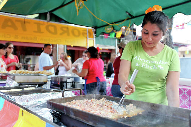 Dulce Guzman cooks chicken for gorditas in Market Square Sunday May 13, 2012, during the Mother's Day Week-end Celebration. Photo: EDWARD A. ORNELAS, SAN ANTONIO EXPRESS-NEWS / © SAN ANTONIO EXPRESS-NEWS (NFS)