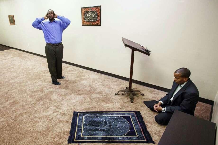 Joseph F. Clark, left, sounds a call to prayer as Imam Khalis Rashaad prays during a service Friday at the Ibrahim Islamic Center. The mosque is unique to Houston because of its concentration on human services and its location, in the Third Ward. Photo: Michael Paulsen / © 2012 Houston Chronicle