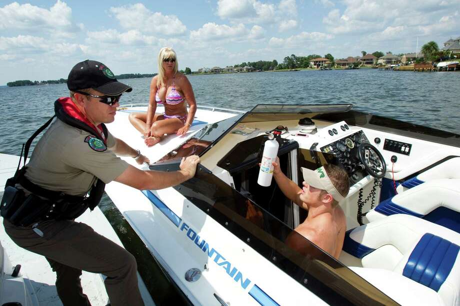 Game Warden Brannon Meinkowsky does a safety check Sunday on Lake Conroe with boater Derek Barber  as Alice Rogers sits on the bow. Safety officials say widespread use of life jackets could save many boaters' lives. Photo: Brett Coomer / © 2012 Houston Chronicle