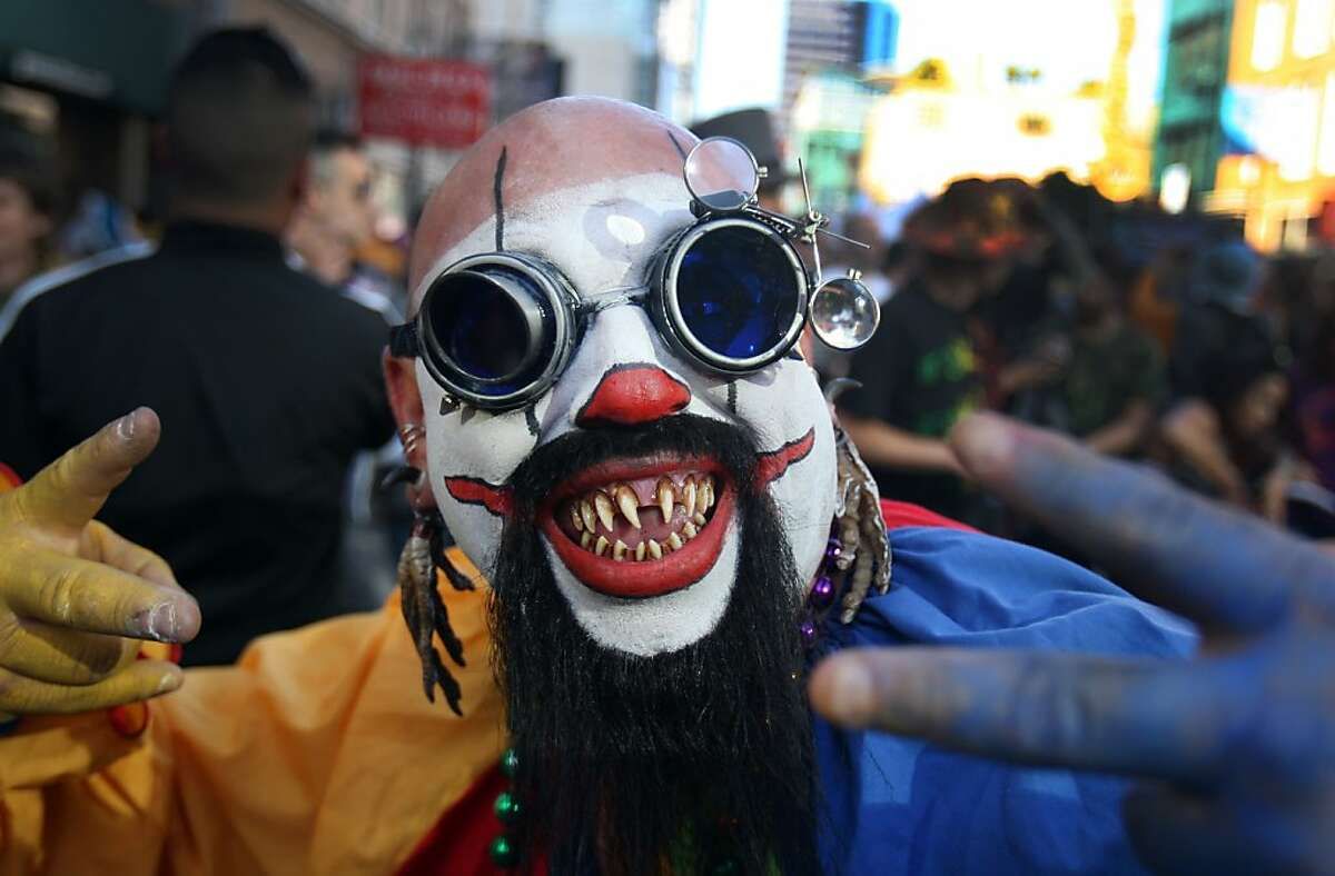 Fred Arrollo, dressed in an elaborate clown costume, dances among a large crowd of people during the How Weird Street Festival in San Francisco on Sunday. Thousands of people dressed in outlandish costumes gathered and 2nd and Howard Street in San Francisco on Monday for music, dancing, and drinks for the annual How Weird Street Festival.