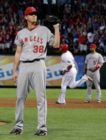 Los Angeles Angels' Jered Weaver (36) waits for a new ball as Texas Rangers' Nelson Cruz, rear, runs the bags following his grand slam in the third inning of a baseball game, Sunday, May 13, 2012, in Arlington, Texas. Photo: AP