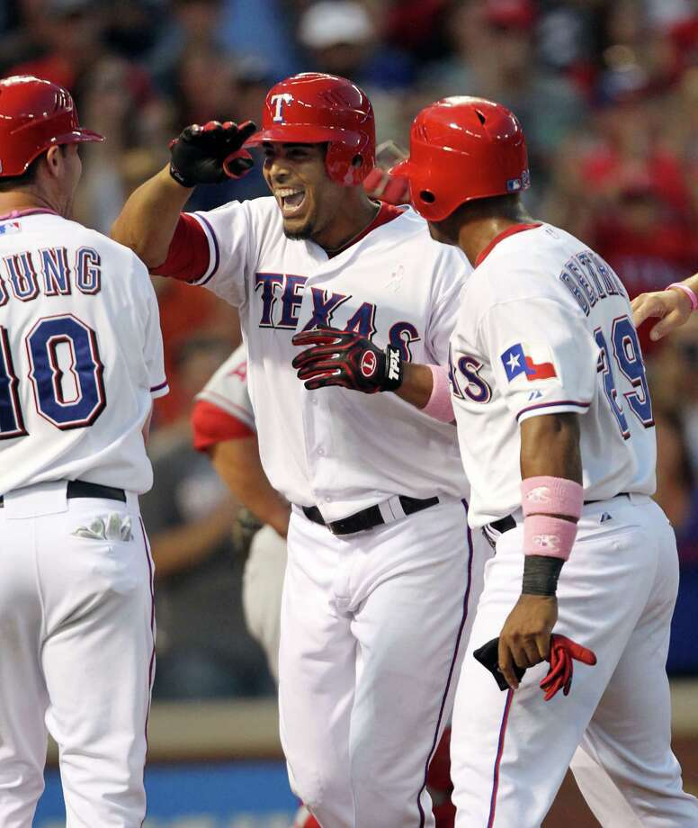 ARLINGTON, TX - MAY 13: Nelson Cruz #17 of the Texas Rangers celebrates with teammates Michael Young #10 and Adrian Beltre #29 after hitting a grand slam home run against pitcher Jered Weaver of the Los Angeles Angels on May 13, 2012 in Arlington, Texas. Photo: Layne Murdoch, Getty Images / 2012 Getty Images