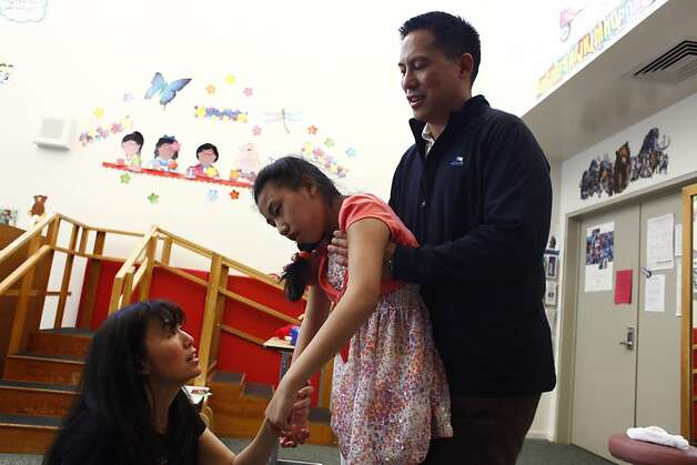 John Corpus (right), CEO of Milyoni, helps his daughter Samantha Corpus (center) stand as his wife Kathy Corpus (left) helps put on her shoes after Samantha's occupational therapy session at the Mauzy Medical Therapy Unit on Monday, May 7, 2012 in Alamo, Calif. Photo: Lea Suzuki, The Chronicle