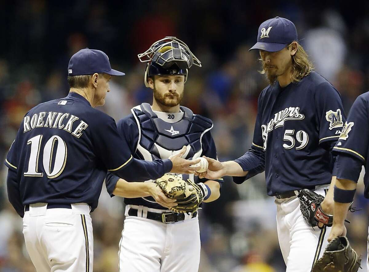 Milwaukee Brewers catcher Jonathan Lucroy watches as manager Ron Roenicke (10) takes relief pitcher John Axford (59) out during the ninth inning of a baseball game against the Chicago Cubs Friday, May 11, 2012, in Milwaukee. The Cubs scored three runs in the inning. (AP Photo/Morry Gash)