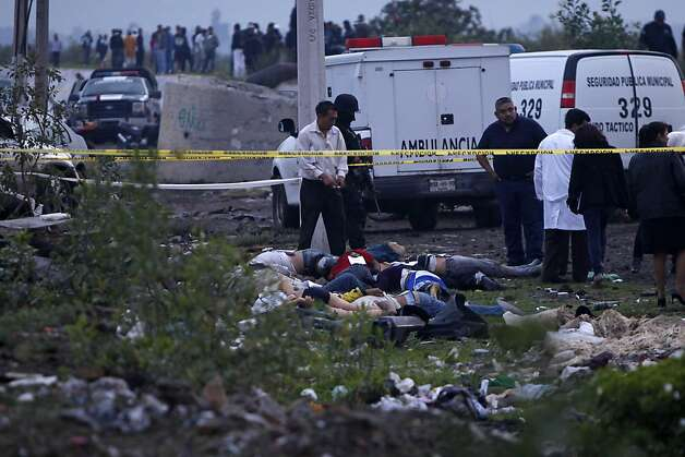 FILE - In this July 8, 2011, file photo, medical workers stand next to bodies in Valle de Chalco, Mexico. The discovery of 49 mutilated bodies dumped on a highway in northern Mexico on Sunday, May 13, 2012, appears to be part of an increasingly gruesome war of intimidation among Mexican drug gangs. (AP Photo/Moises Castillo, file) Photo: Moises Castillo, Associated Press