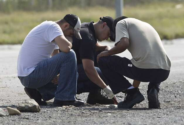 Forensic experts examine the area where dozens of bodies, some of them mutilated, were found on a highway connecting the northern Mexican metropolis of Monterrey to the U.S. border in the town of San Juan near the city of Monterrey, Mexico,  Sunday, May 13, 2012. (AP Photo/Christian Palma) Photo: Christian Palma, Associated Press