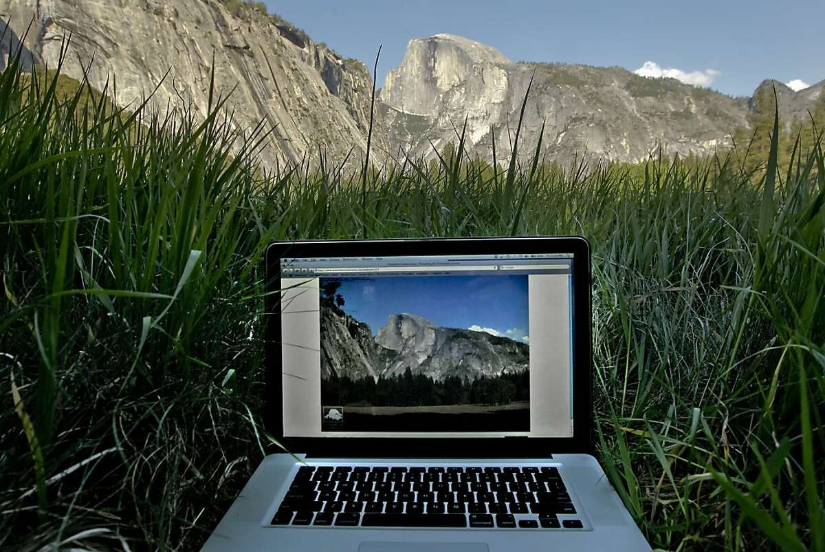 The Yosemite Conservancy feeds a live image of the Ahwahnee Meadow online, (on screen) of the actual scene (above) at Yosemite National Park, on Friday May 11, 2012. The Yosemite Conservancy has installed their latest web cam to give the public live online feeds of Yosemite Falls. They now have several webcam images online to give visitors views of El Capitan, Half Dome, views from Sentinel Dome and now Yosemite Falls.