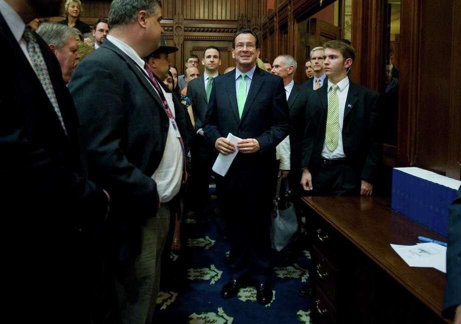 Gov. Dannel P. Malloy, center, smiles as he is introduced to address the General Assembly at the end of session at the Capitol in Hartford, Conn., Thursday, May 10, 2012.  The session resolved several high-profile, perennial issues including the state's death penalty, medical marijuana usage and Sunday alcohol sales. Photo: Jessica Hill, Jessica Hill/Associated Press / AP2012  Associated Press