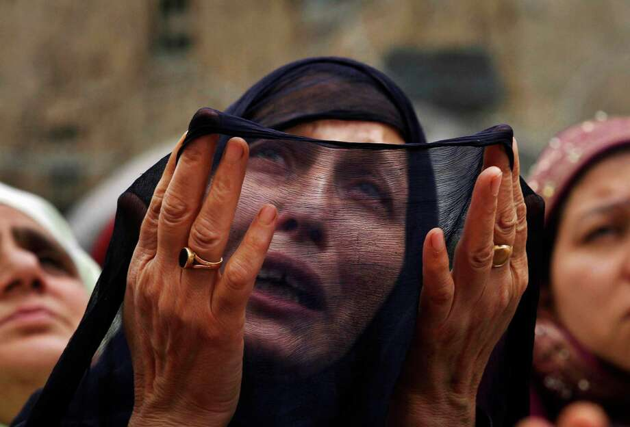 A Kashmiri Muslim woman prays as a head priest, unseen, displays a relic, believed to be a hair from the beard of the Prophet Mohammad, during special prayers on the death anniversary of Abu Bakr Siddiq, the first Caliph of Islam at Hazratbal Shrine on the outskirts of Srinagar, India, Monday, May 14, 2012. (AP Photo/Mukhtar Khan) Photo: Mukhtar Khan, Associated Press / AP