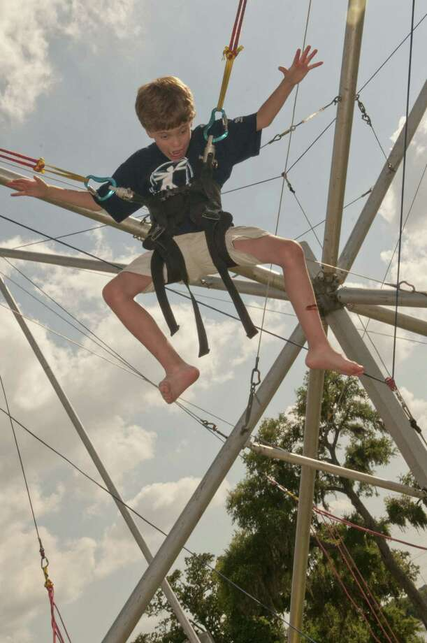 Angus Heartsill, 10 of El Lago enjoys the jumping ride at the Texas Music Festival held Saturday at Walter Hall Park in League City. Photo: Kim Christensen, For The Chronicle / ©Kim Christensen Photography