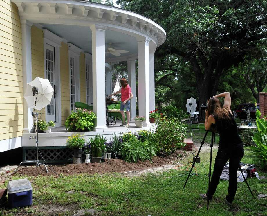 """Jill Hunter, right, of Jill Hunter Photography out of Houston, waits for Photo Stylist Kay Bay, to move a pitcher of tea on a table, as she prepares to shoot the round porch May 10, 2012.  Beth Wheeler has been renovating her turn of the century home in Orange for the past ten years. After entering her home into a """"This Old House"""" magazine contest the national publication has decided to photograph her home for the front cover of it's July's issue.  Dave Ryan/The Enterprise Photo: Dave Ryan"""