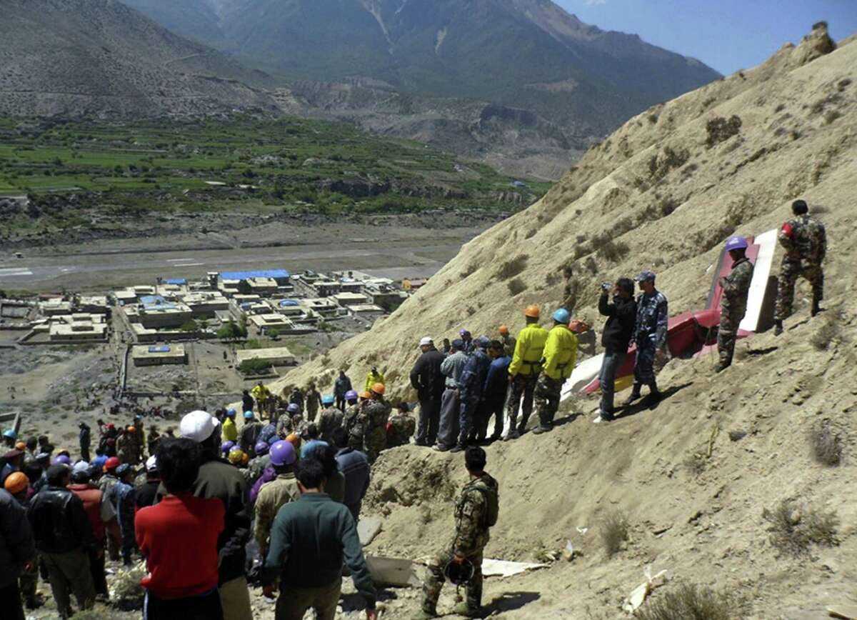 Nepalese rescue workers and officials inspect the site of a plane crash near Jomsom, 125 miles northwest of the capital, Katmandu, Nepal, Monday. The plane crashed into a mountain in the Himalayas while trying to land at an airport in northern Nepal on Monday, killing 15 people and critically injuring six.
