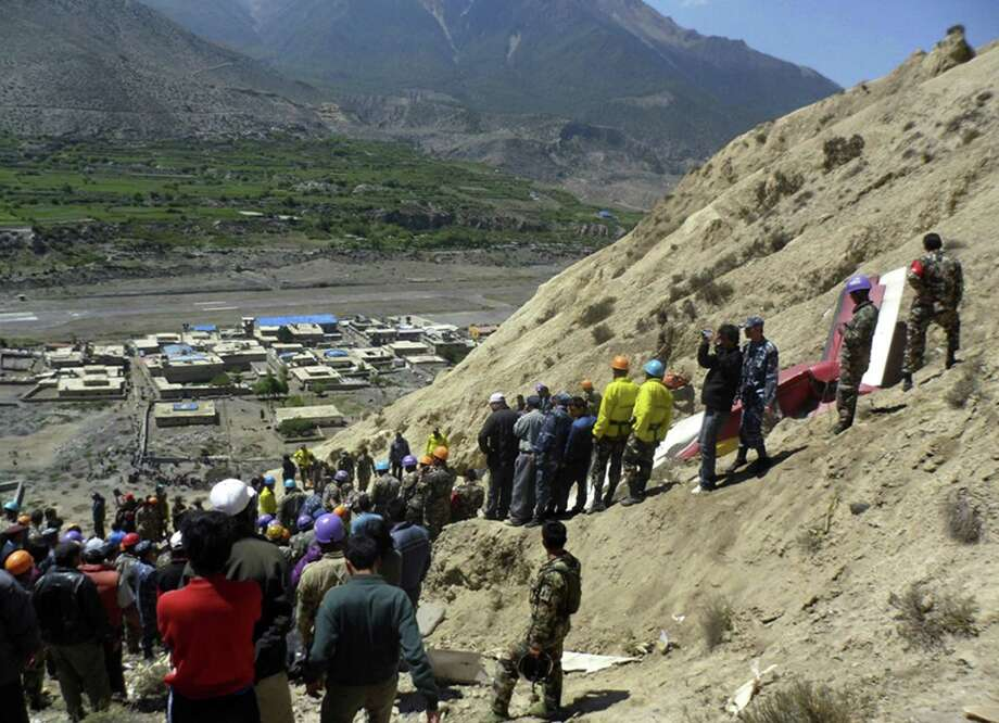 Nepalese rescue workers and officials inspect the site of a plane crash near Jomsom, 125 miles northwest of the capital, Katmandu, Nepal, Monday.  The plane crashed into a mountain in the Himalayas while trying to land at an airport in northern Nepal on Monday, killing 15 people and critically injuring six. Photo: AP