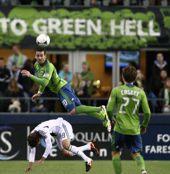 Sounder's defender Zach Scott heads the ball above Galaxy player Mike Magee during the Galaxy vs. So