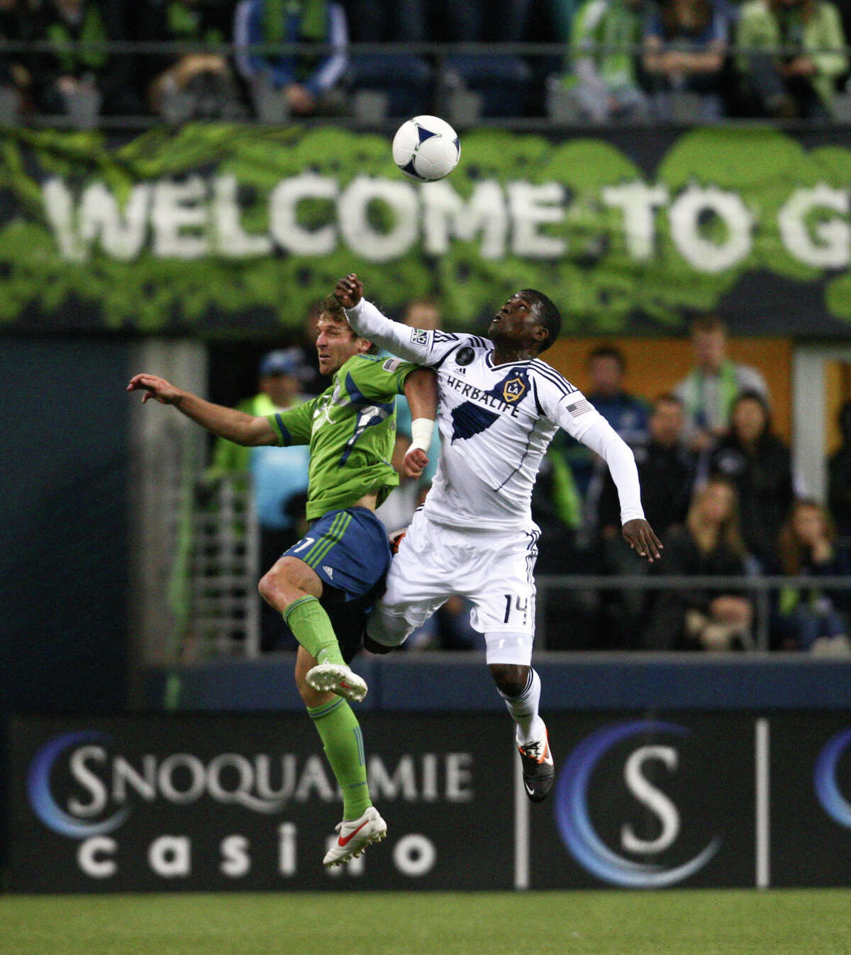 Sounder's midfielder Alex Caskey and Galaxy player Edson Buddle collide in the air.