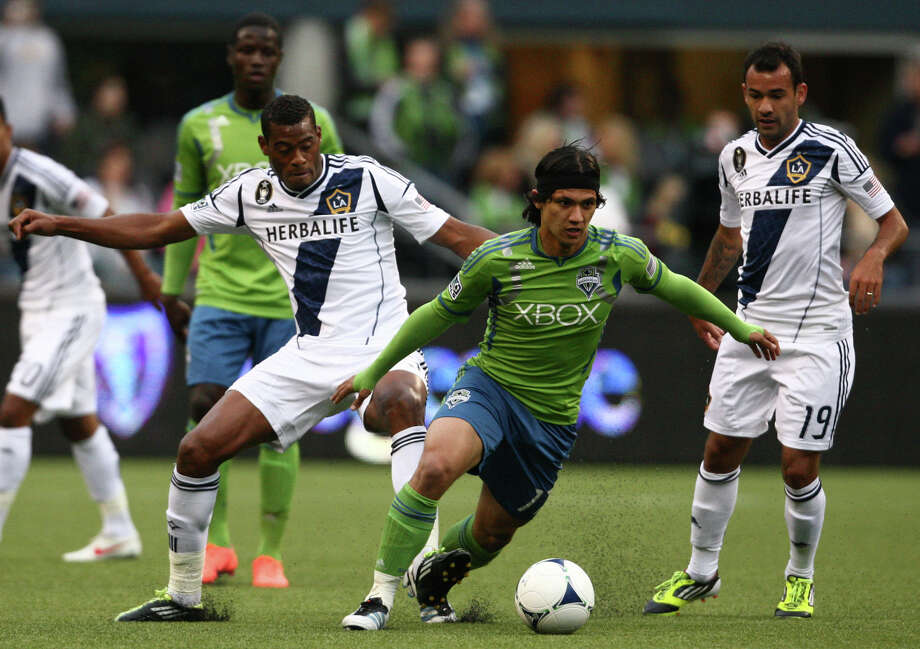 Fredy Montero dribbles ahead of LA Galaxy players David Junior Lopes and Juninho. Photo: SOFIA JARAMILLO / SEATTLEPI.COM