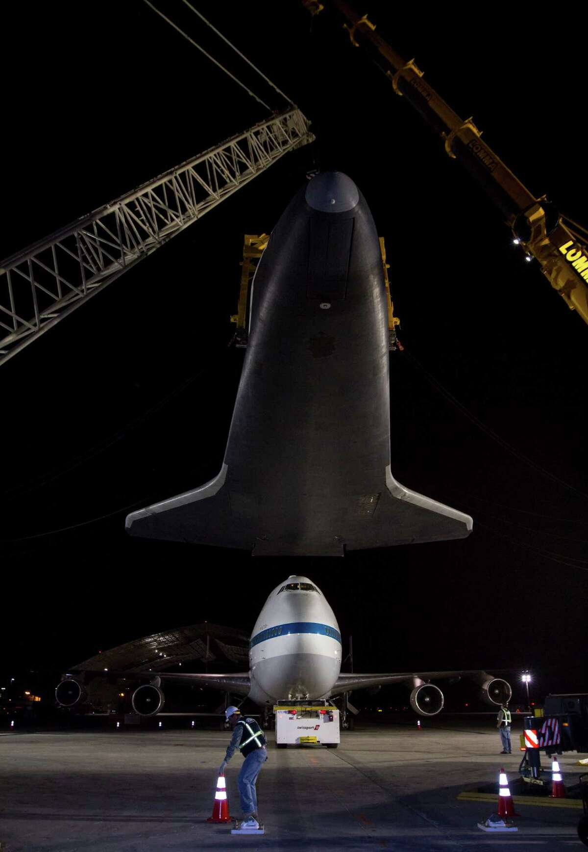 In this photo provided by NASA, space shuttle Enterprise is held aloft by a yellow sling and a set of cranes after it was removed from the top of NASA's 747 Shuttle Carrier Aircraft early Sunday morning, May 13, 2012 at John F. Kennedy International Airport in New York. The 747 was towed backwards so that Enterprise could be lowered. The shuttle will be placed on a barge that will move by tugboat up the Hudson River to the Intrepid Sea, Air & Space Museum in June. The shuttle will be lifted by crane and placed on the flight deck of the Intrepid, where it will be on exhibit to the public starting this summer in a temporary climate-controlled pavilion. (AP Photo/NASA, Kim Shiflet) MANDATORY CREDIT