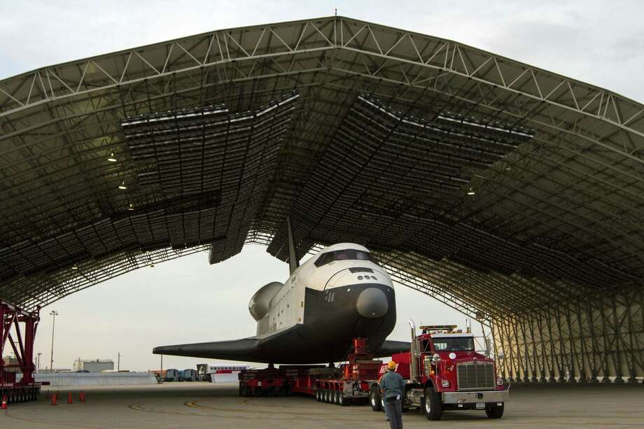 "TOPSHOTS  The US space shuttle Enterprise, mounted on transport vehicle, is backed into a temporary hanger after being demated from the NASA 747 Shuttle Carrier Aircraft (SCA) at John F. Kennedy (JFK) International Airport in Jamaica, New York, Sunday, May 13, 2012. Enterprise will be placed on a barge that will move by tugboat up the Hudson River to the Intrepid Sea, Air & Space Museum in June. The shuttle will be lifted by crane and placed on the flight deck of the Intrepid, where it will be on exhibit to the public starting this summer in a temporary climate-controlled pavilion.    AFP PHOTO / NASA / Kim SHIFLET    == RESTRICTED TO EDITORIAL USE / MANDATORY CREDIT:  ""AFP PHOTO /  NASA / Kim SHIFLET"" / NO SALES / NO MARKETING / NO ADVERTISING CAMPAIGNS / DISTRIBUTED AS A SERVICE TO CLIENTS ==Kim Shiflet/AFP/GettyImages Photo: KIM SHIFLET, AFP/Getty Images / AFP"