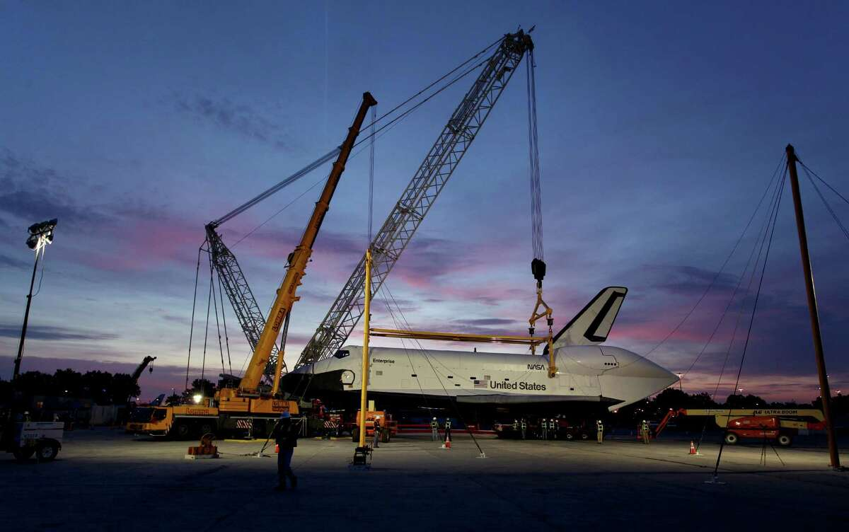The sun rises as the space shuttle Enterprise rests on a specialized transporter after it was lifted from a NASA 747 Shuttle Carrier Aircraft at John F. Kennedy International Airport in New York, Sunday, May 13, 2012, in preparation for its upcoming journey to its new home at the Intrepid Sea, Air & Space Museum. Enterprise has been separated from the NASA 747 Shuttle Carrier at John F. Kennedy International Airport, just weeks after flying over New York City. Next month it will be taken by barge to the aircraft carrier USS Intrepid, the floating air-and-space museum that will be the shuttleÃ'Â's permanent home. The shuttle is scheduled to open to the public in mid-July.