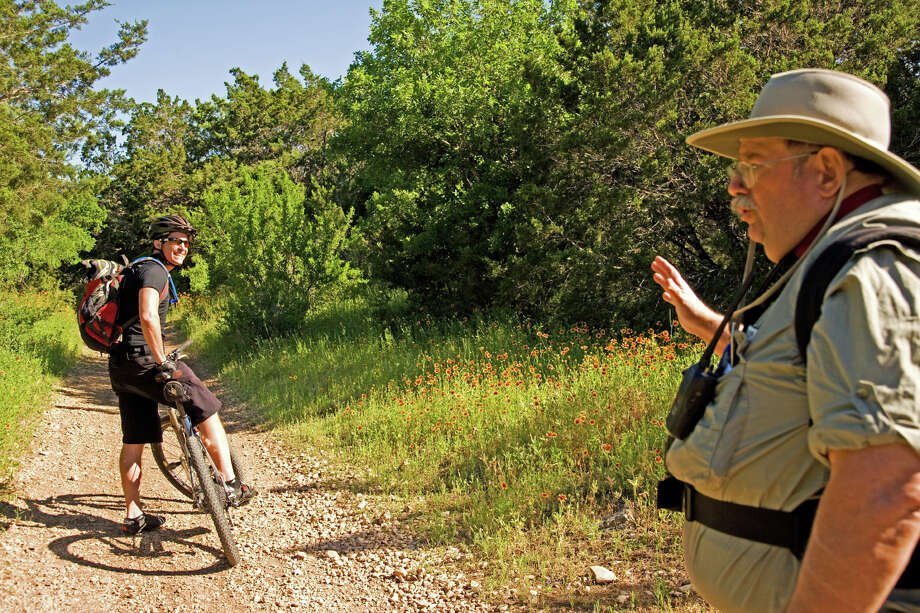 Bicyclist David Rogers pauses to chat with Steve Hawkins, a volunteer with Friends of Government Canyon who guides the Explore the Canyon Hike. Photo: JOHN GOODSPEED/FOR THE EXPRESS-NEWS