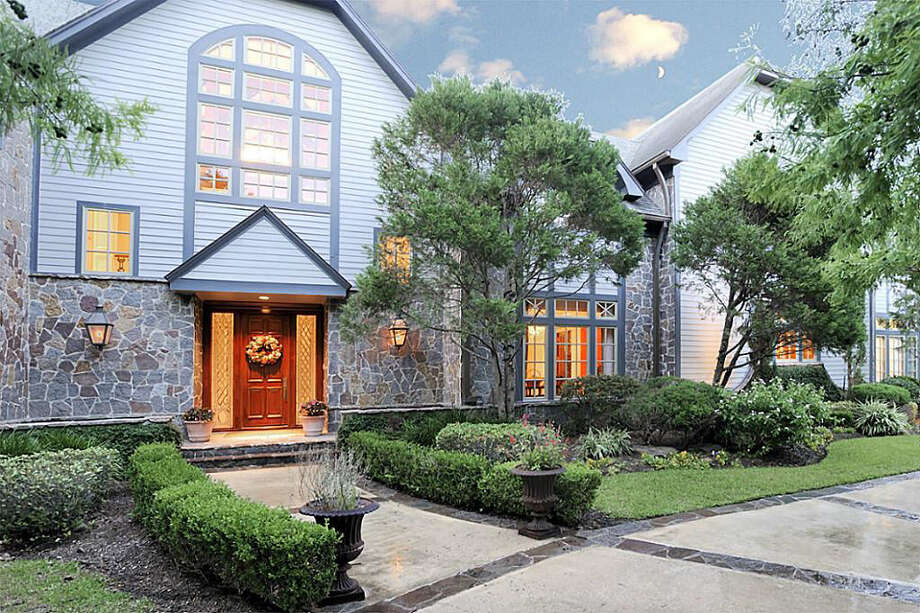 A look at the front exterior of the home, spotlighting the architecture of the home as well as the professionally landscaped yard and circular driveway. Photo: Realtor.com