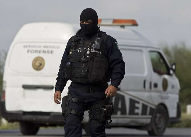 A federal policeman guards the area where dozens of bodies, some of them mutilated, were found on a highway connecting the northern Mexican metropolis of Monterrey to the U.S. border found in the town of San Juan near the city of Monterrey, Mexico,  Sunday, May 13, 2012. (AP Photo/Christian Palma) Photo: Christian Palma, Associated Press