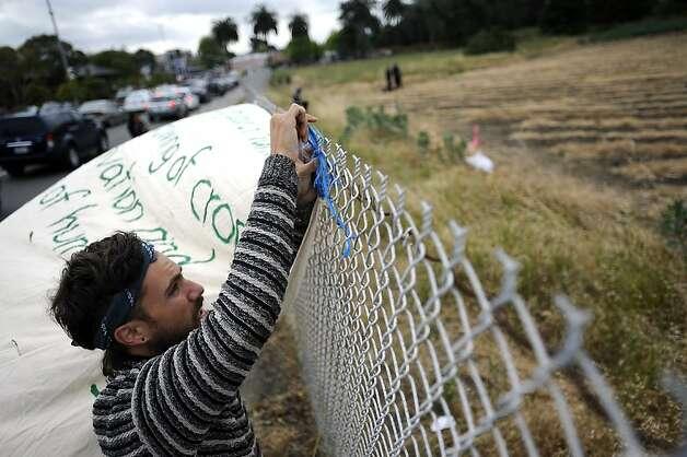 A protester that wished to not give a name hangs a sign on the outside of the fence that surrounds the Gill Tract.  Police raided and cleared out protesters with Occupy the Farm at the Gill Tract in Albany, CA Monday May 14th, 2012 Photo: Michael Short, Special To The Chronicle
