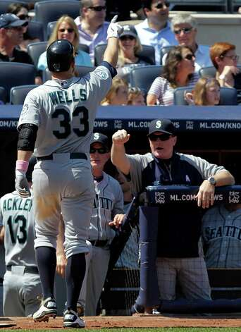 Seattle Mariners' Casper Wells (33) celebrates as he returns to the dugout after hitting a two-run home run during the sixth inning of a baseball game against the New York Yankees at Yankee Stadium in New York, Sunday, May 13, 2012. (AP Photo/Seth Wenig) Photo: Seth Wenig