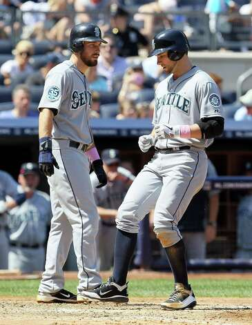 NEW YORK, NY - MAY 13:  Casper Wells #33 (R) of the Seattle Mariners celebrates his sixth inning two run home run against the New York Yankees with teammate Dustin Ackley #13 at Yankee Stadium on May 13, 2012  in the Bronx borough of New York City.  (Photo by Jim McIsaac/Getty Images) Photo: Jim McIsaac